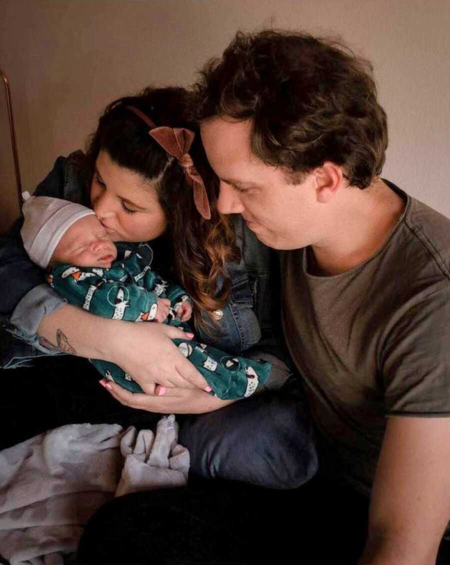 New parents hold their newborn child during newborn photoshoot