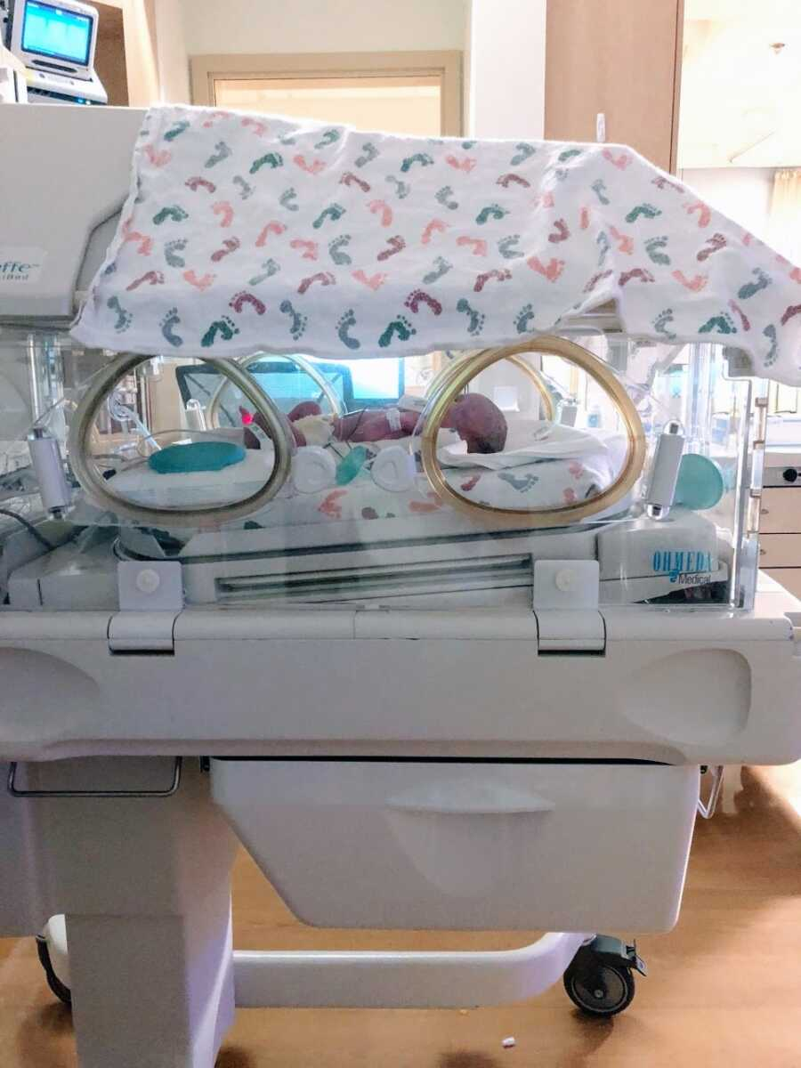 Mom snaps a photo of her third child sleeping in an isolette in the NICU