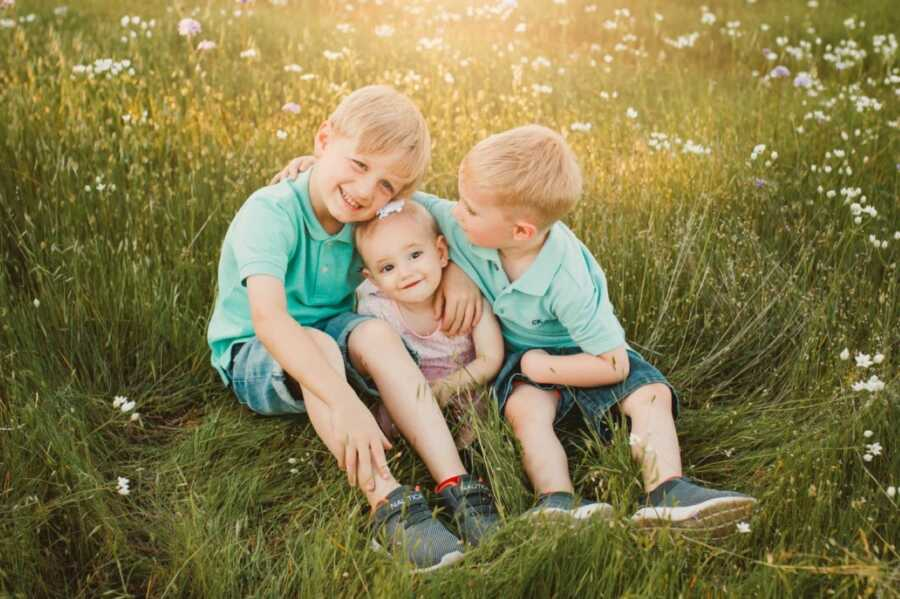 Mom takes a photo of her three children, two boys in matching outfits and one younger daughter