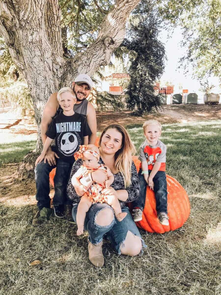 Family of five take photos together with pumpkins in Halloween-themed photos to celebrate the fall season