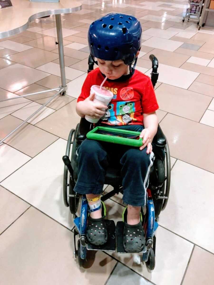 Little boy sits in a wheelchair and sips from a drink while wearing a blue helmet
