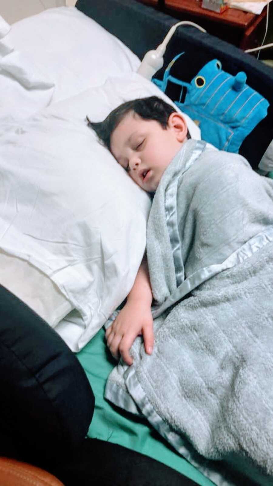 Little boy battling unknown seizures sleeps in a hospital bed with a Thomas the Train stuffed toy right next to him