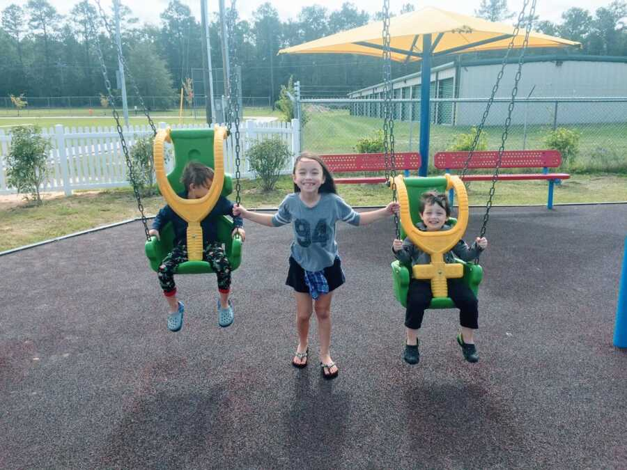 Mom snaps a photo of her three kids playing on the playground together