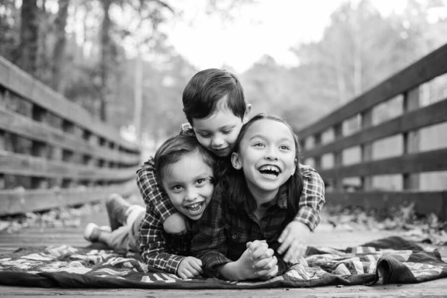 Three siblings take a photo together for a fall photoshoot while laying on a blanket on a wooden bridge
