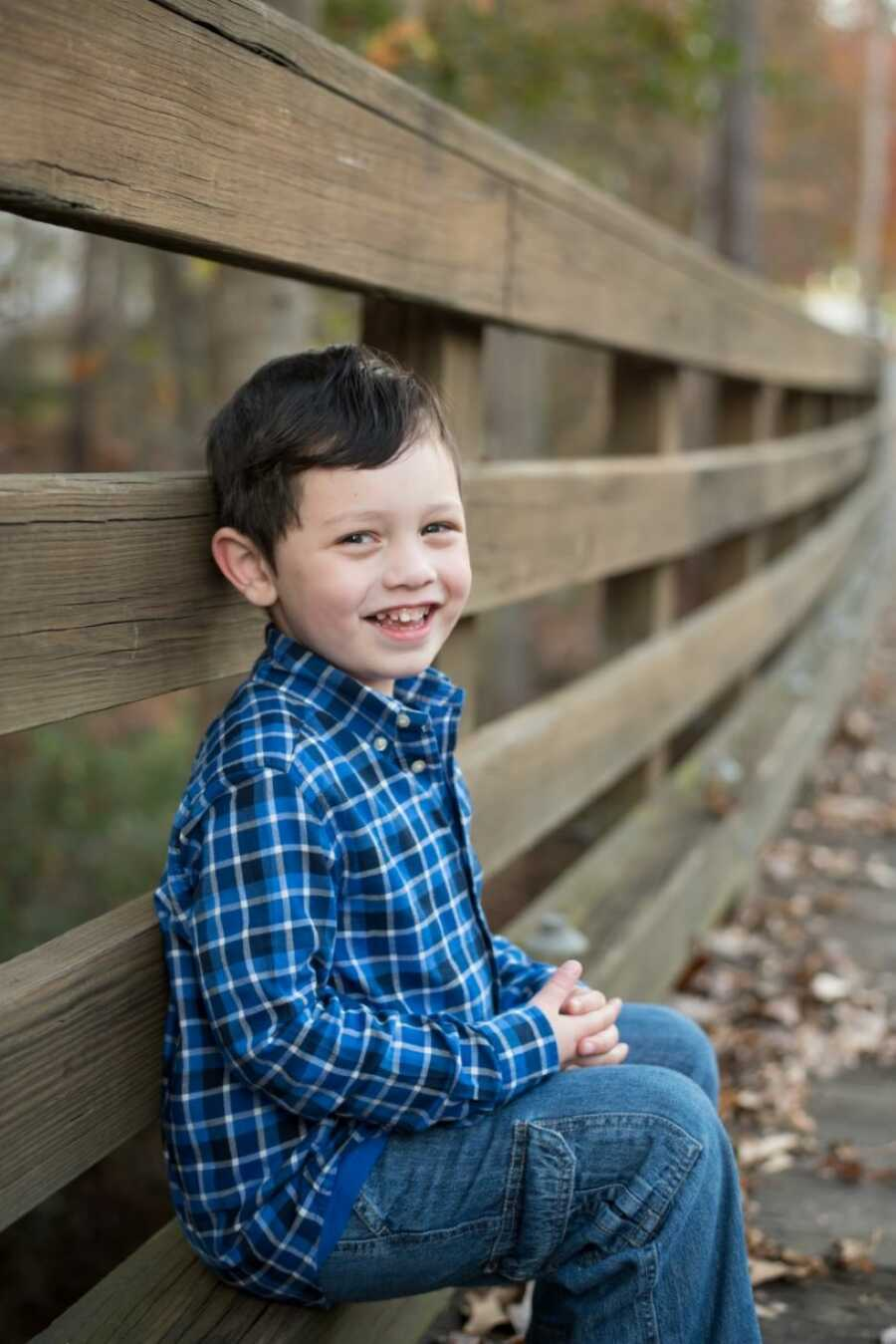 Little boy smiles big for a photo while wearing a blue plaid shirt and blue jeans, sitting down on a wooden bridge