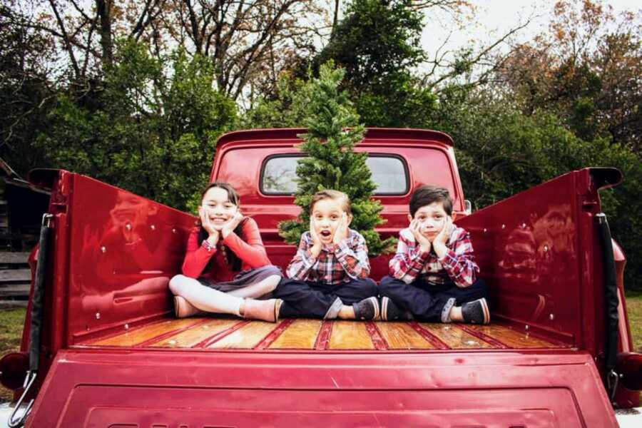Mom shares Christmas photo of her three children sitting in the back of a red pick-up truck with a Christmas tree in it