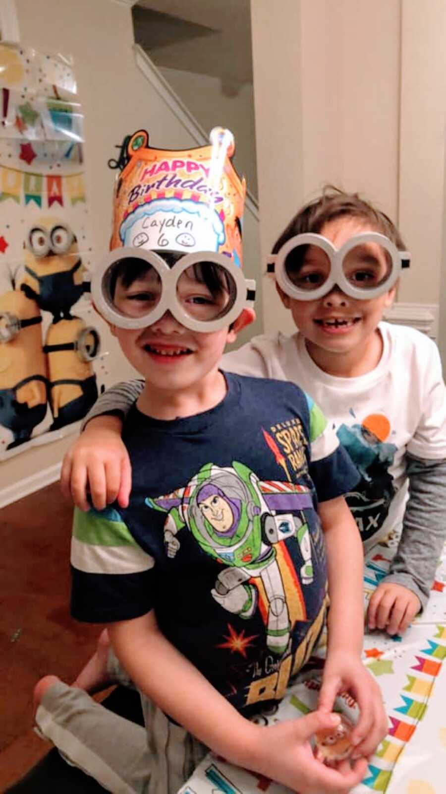 Mom snaps a photo of her two sons having fun at her son's Minion-themed birthday party