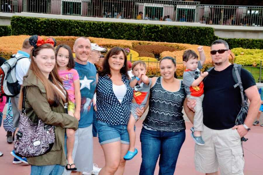 Family take a group photo with their children while at Disneyland in California