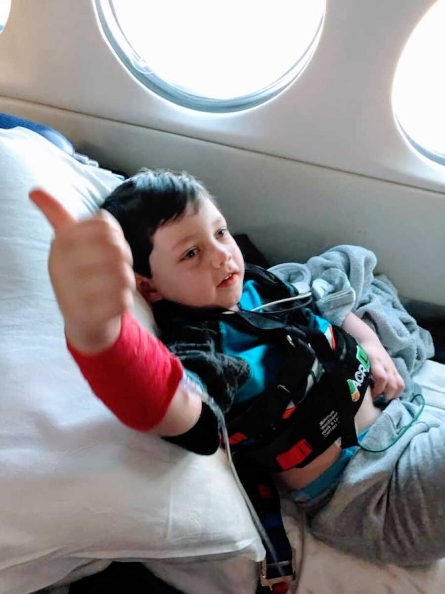 Mom snaps a photo of her son giving her the thumbs up while in a plane on the way to a hospital for his Epilepsy