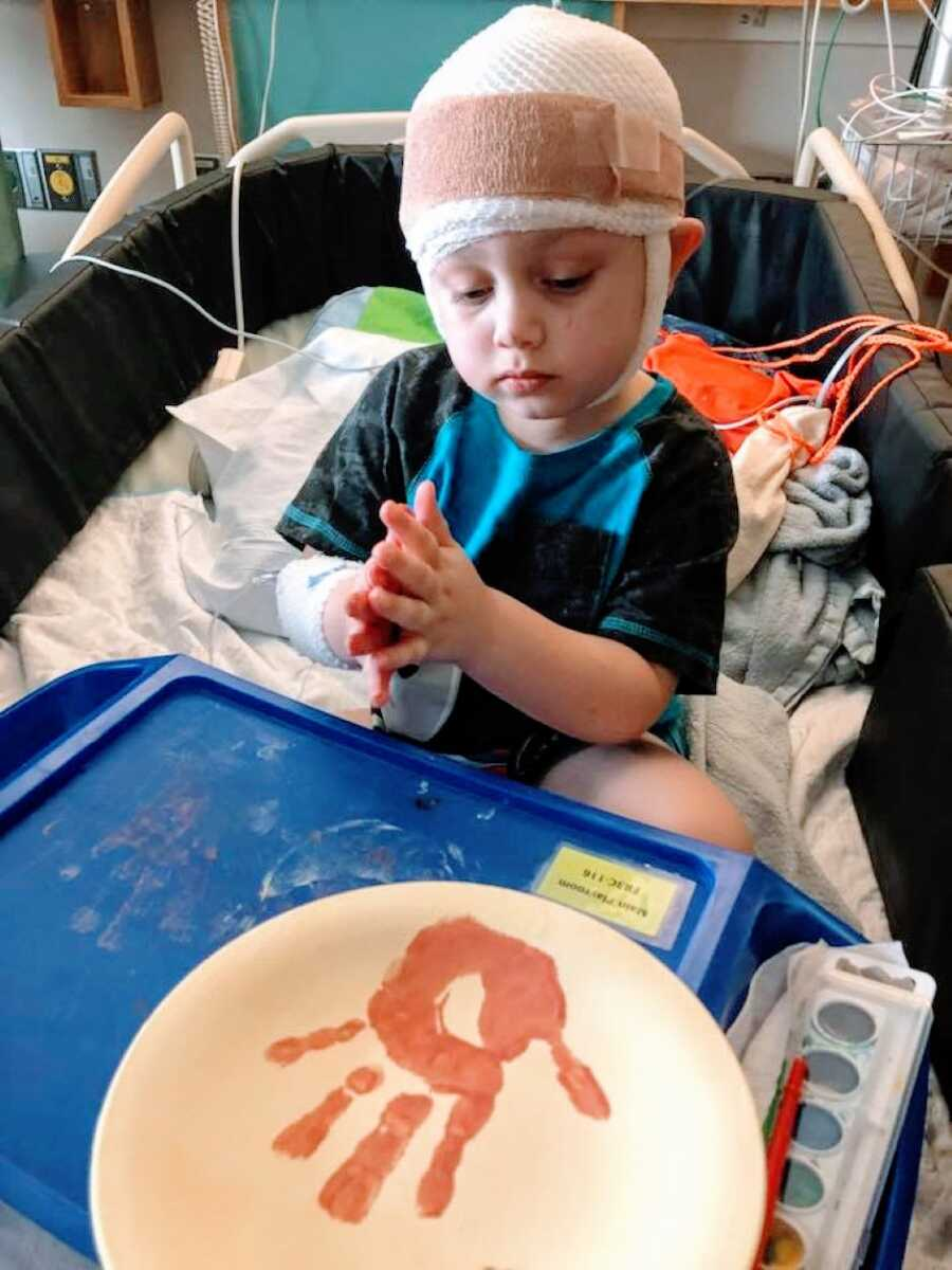 Little boy undergoing EEGs and in-patient therapy practices a craft while in the hospital