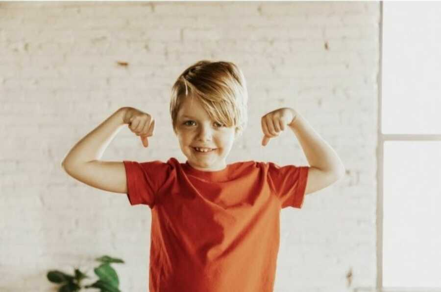 Little boy adopted by his parents poses for a photo, smiling big while showing off his muscles