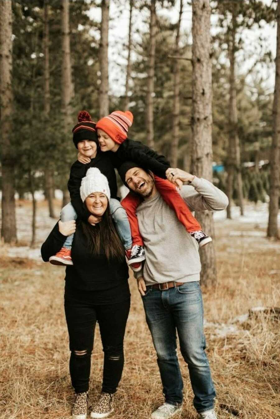 Family of four take a photo together out in the Minnesota cold, all wearing beanies