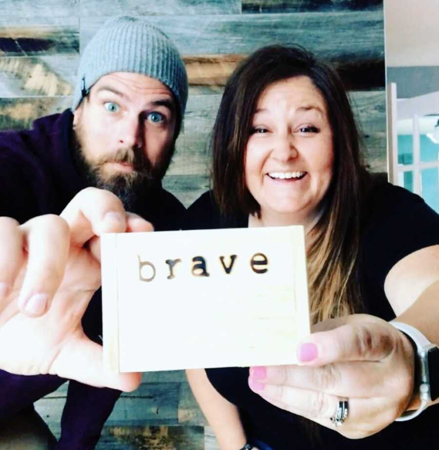 """Couple hoping to adopt a son hold up a wooden box with the word """"Brave"""" engraved into it"""