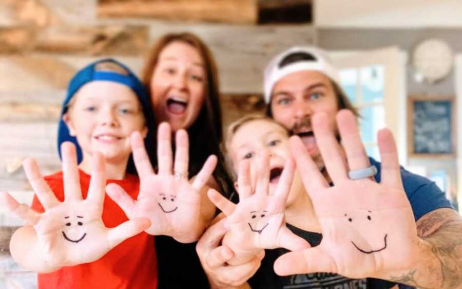 Family of four take a photo together with smiley faces drawn onto their hands