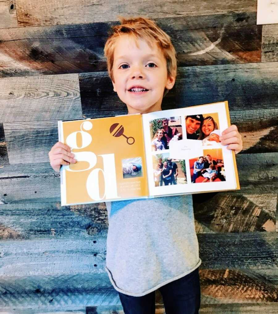 Little boy holds a photobook depicting his adoption and life story