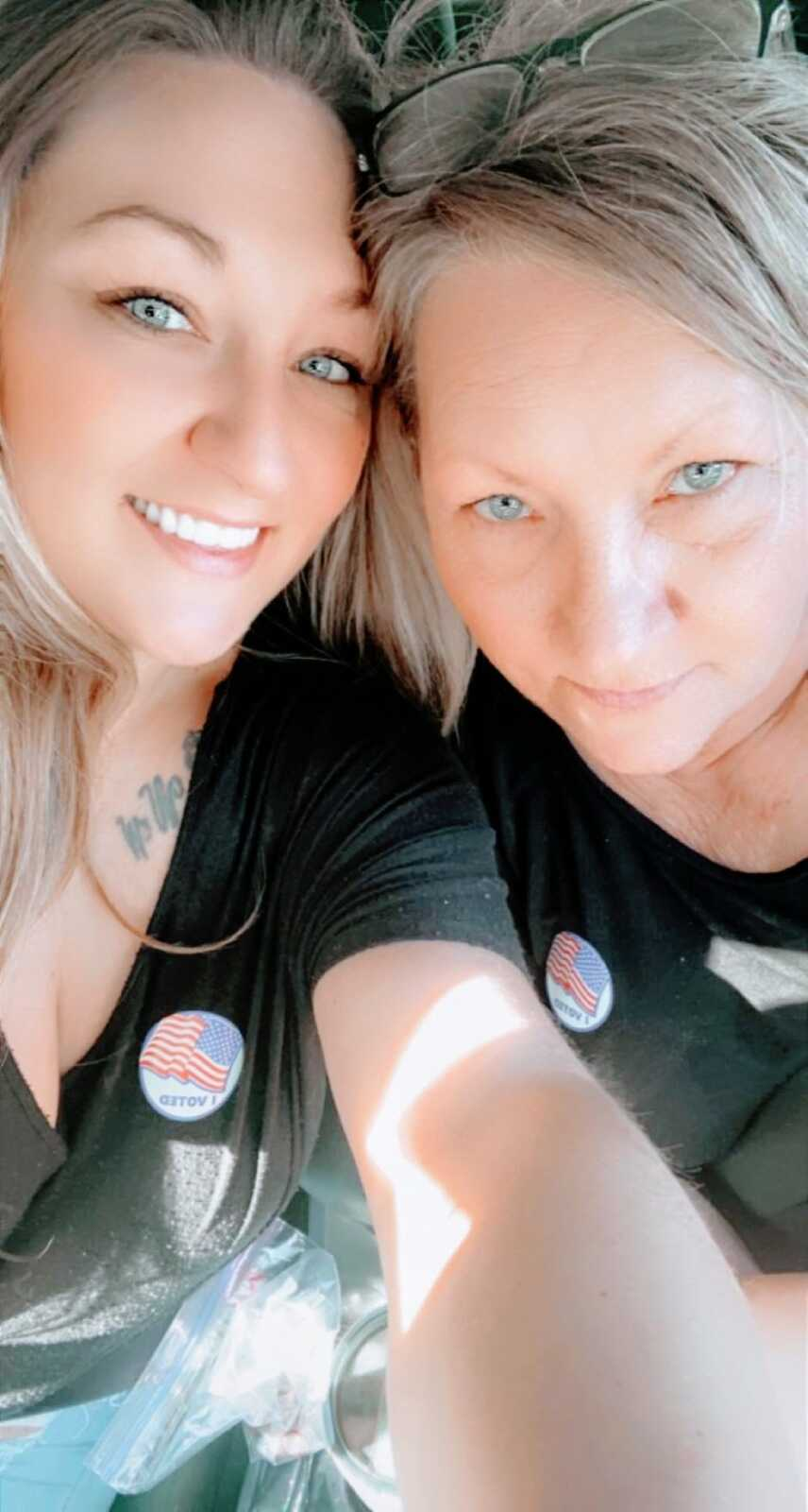 """Young woman takes a selfie with her mom while they both wear black t-shirts and """"I voted"""" stickers"""