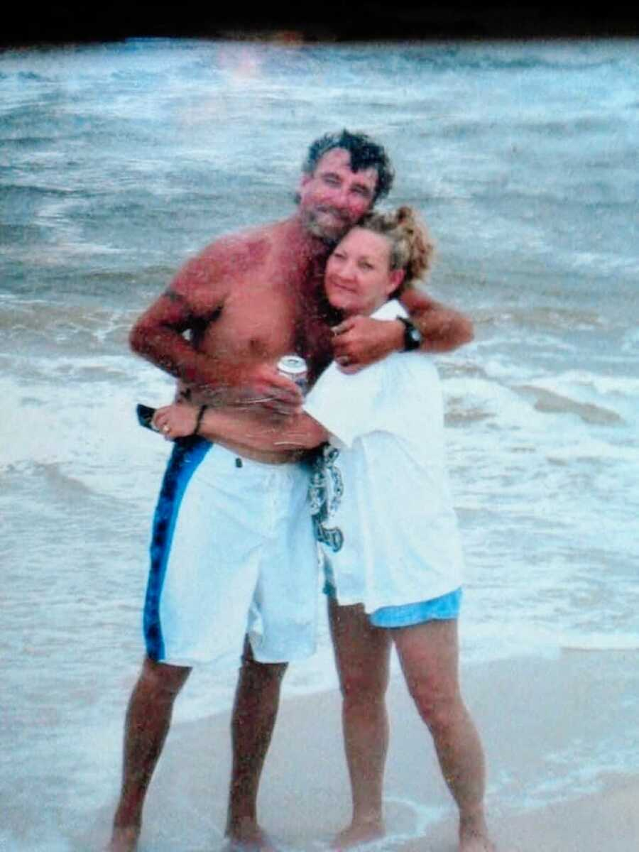 Woman shares an old photo of her mom and stepdad hugging for a photo while enjoying time together at the beach