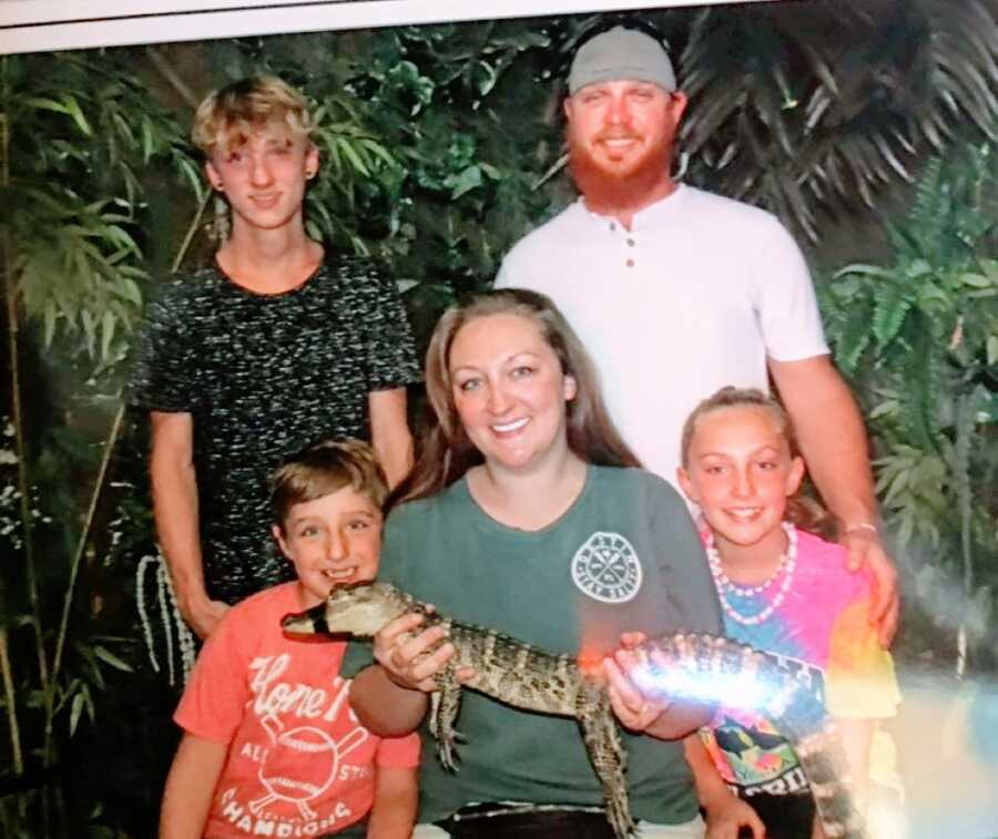 Blended family of five take a photo together while the mom holds a baby alligator with its mouth taped shut