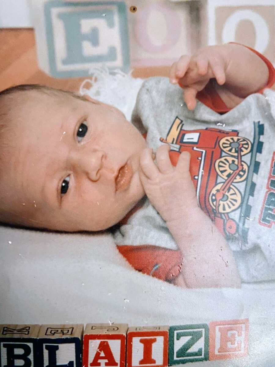 Teen mom takes a photo of her newborn son in a red and gray shirt with a train on it