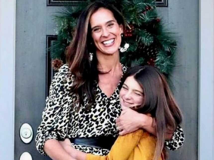 Mom hugs her oldest daughter tight in candid picture on their front porch