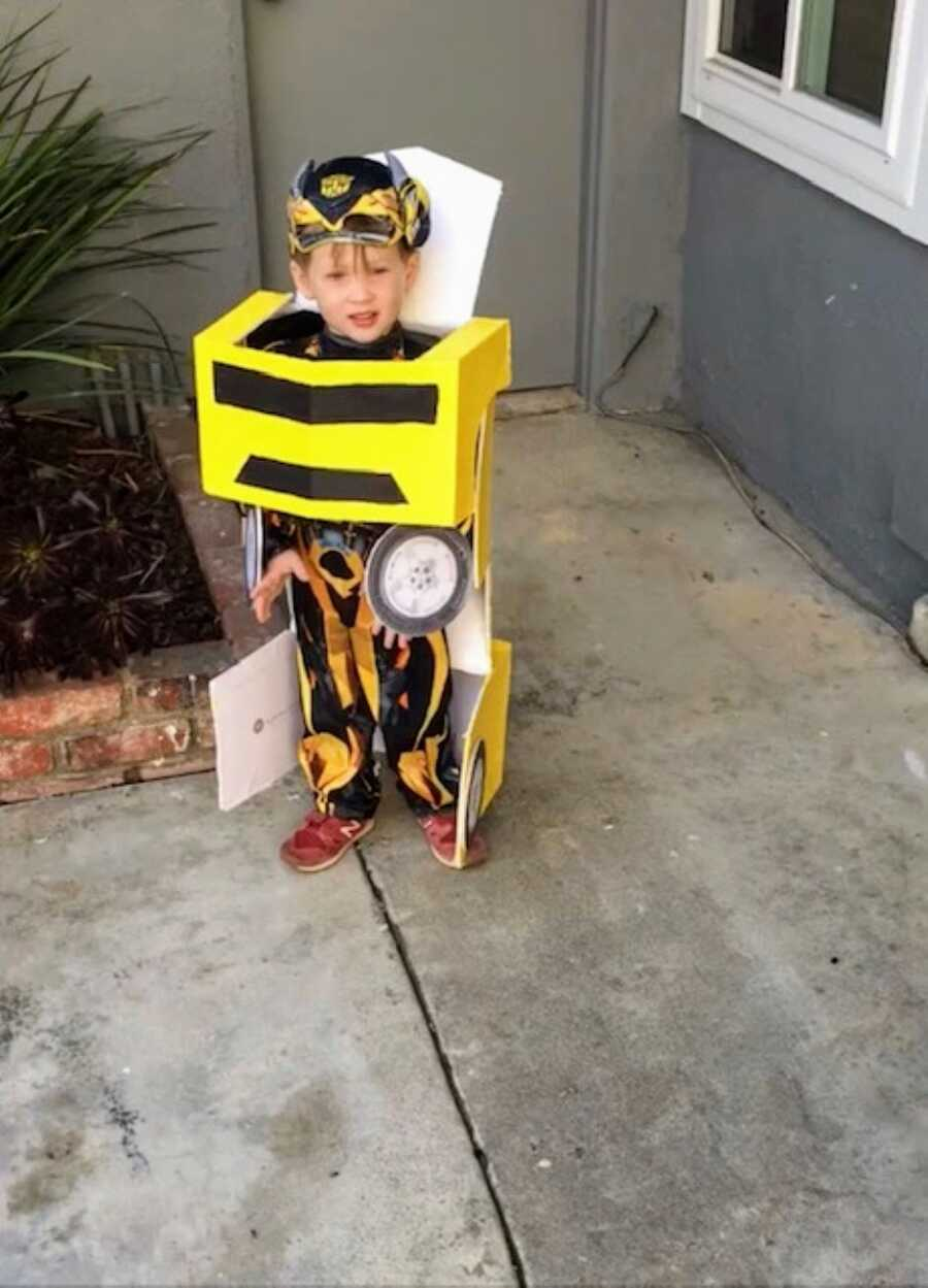 Little boy poses for a photo in a homemade Transformers Bumblebee costume for Halloween