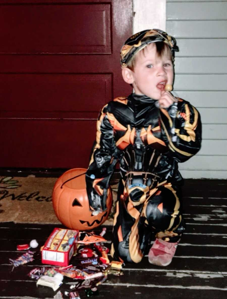 Little boy sits on the front porch after trick or treating in a Bumblebee costume while eating a sucker