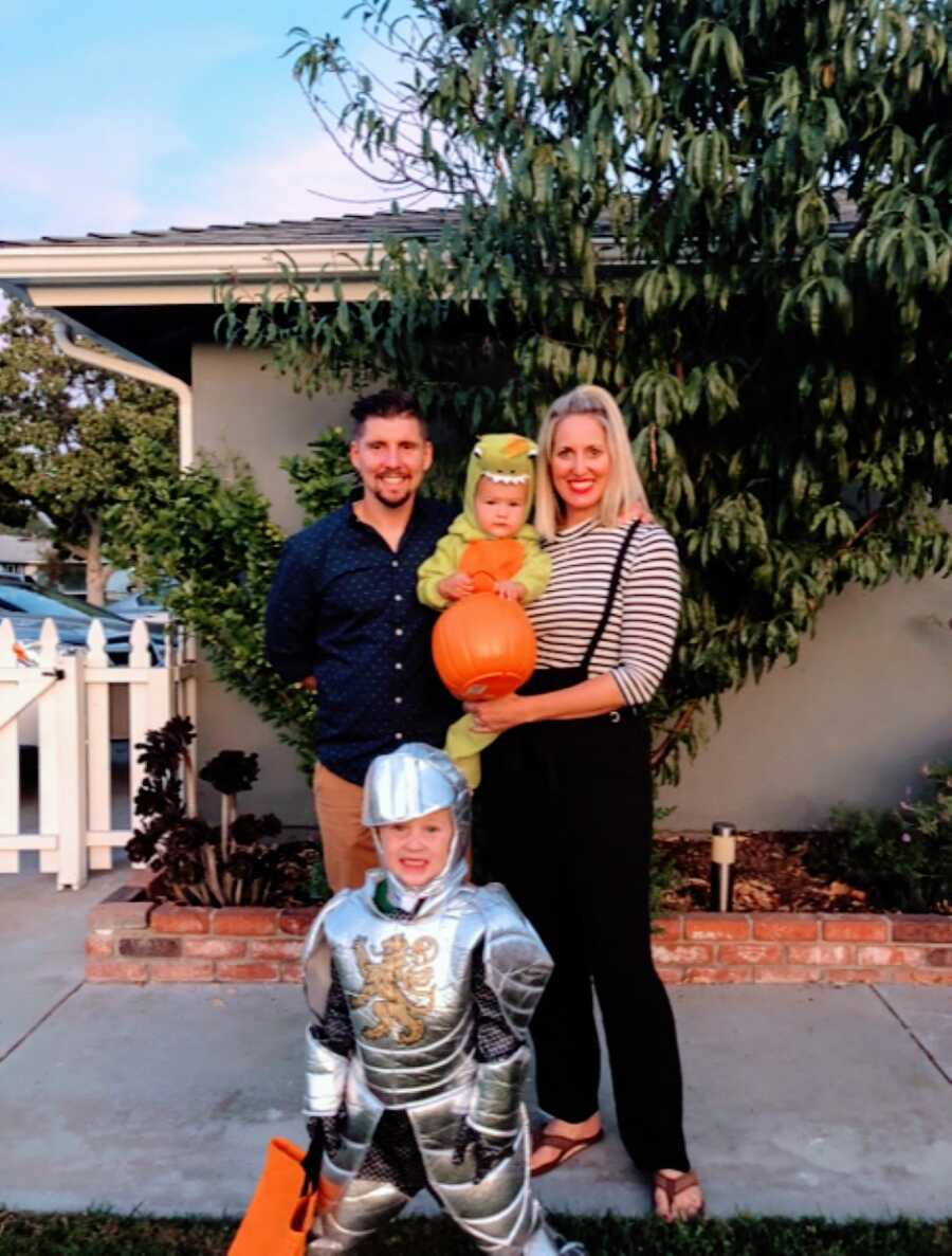 Family of four take a photo together on Halloween, one son dressed as a knight and the other a dinosaur