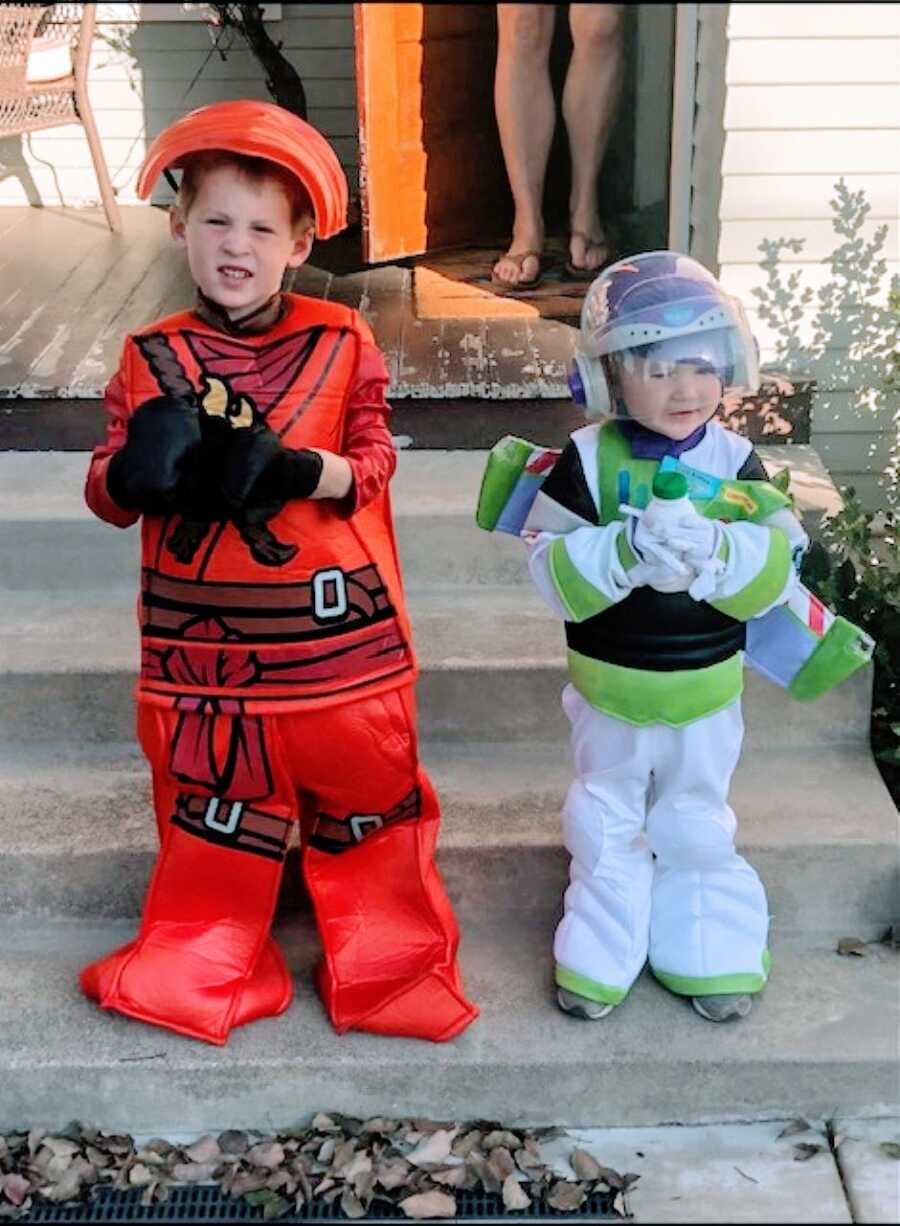Mom snaps a photo of two of her sons in Halloween costumes before trick or treating, one a Lego ninja and the other Buzz Lightyear