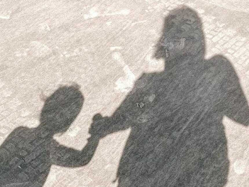 Mom and daughter take a photo of their shadow while walking hand-in-hand