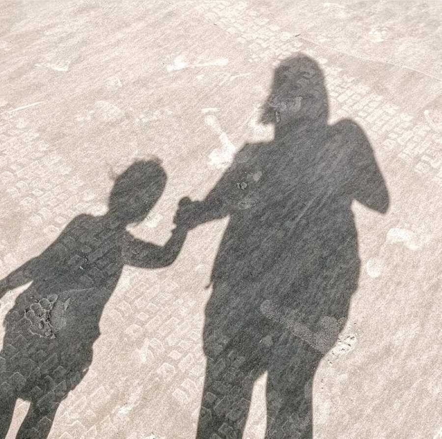 Mom takes a photo of her and her daughter's shadows while they walk together holding hands
