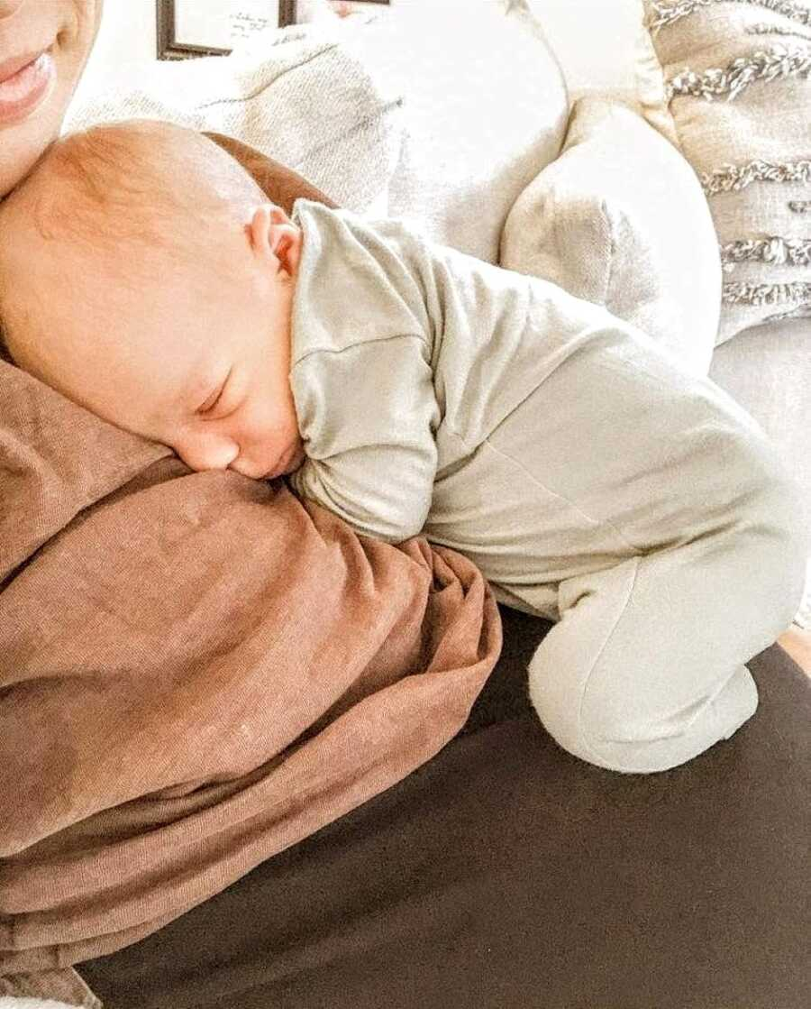 Postpartum mom shares photo of her newborn perfectly cuddling into the folds of her body during some bonding time