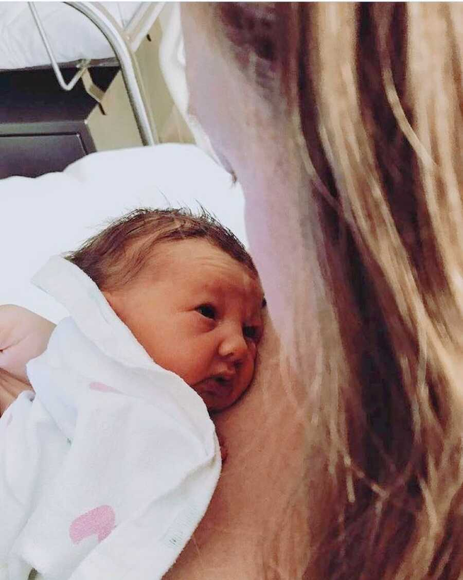 Mom looks down at her newborn daughter while still in the hospital after giving birth