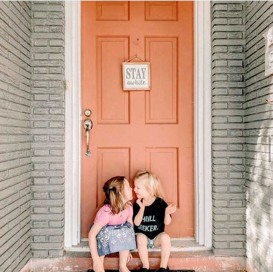 Two sisters pose in front of a their family home's front door while going in to share a kiss