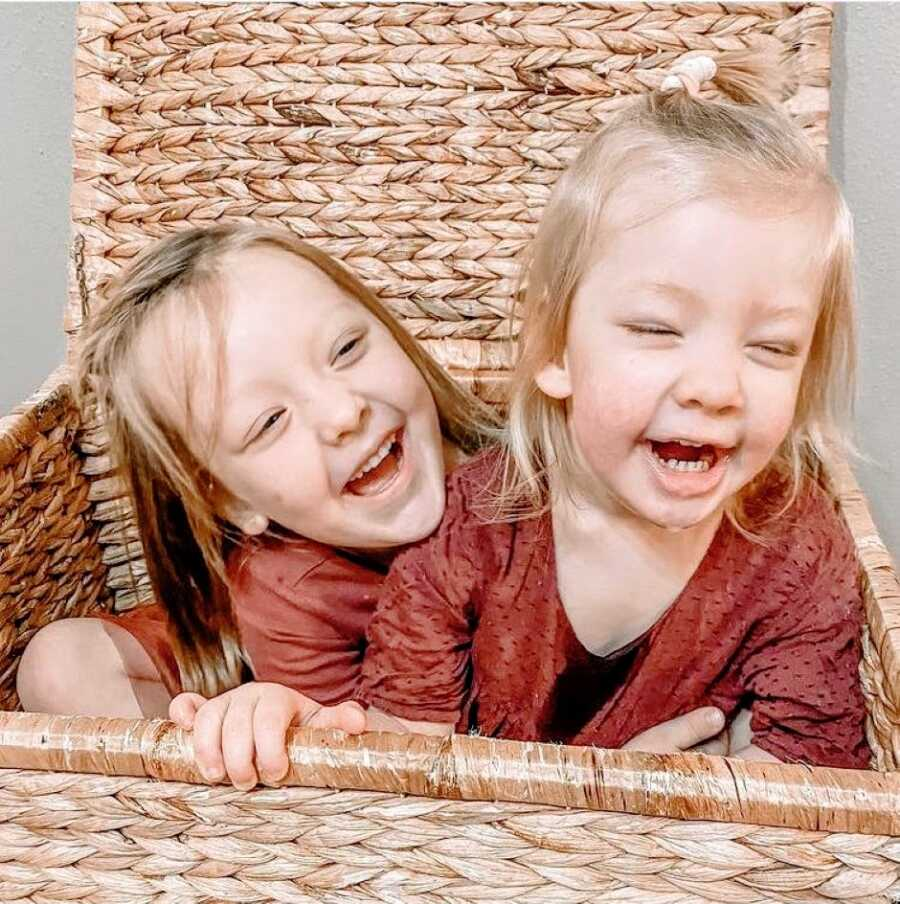 Sisters smile and laugh while playing together in a basket