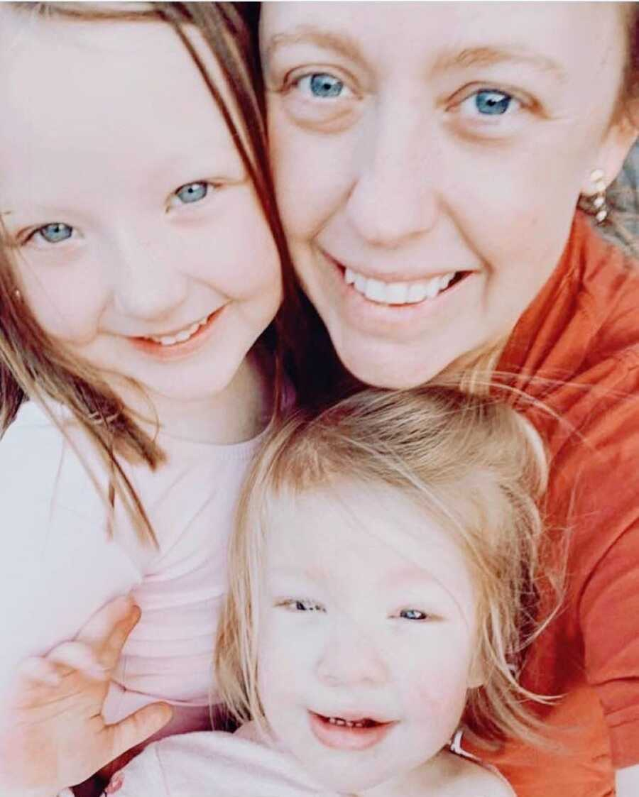 Girl mom takes a selfie with her two daughters, showing how much they all look alike
