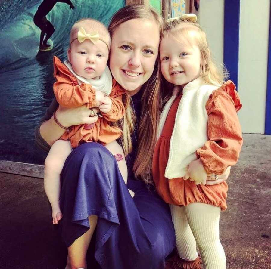 Mom takes a photo with her two daughters wearing matching orange outfits