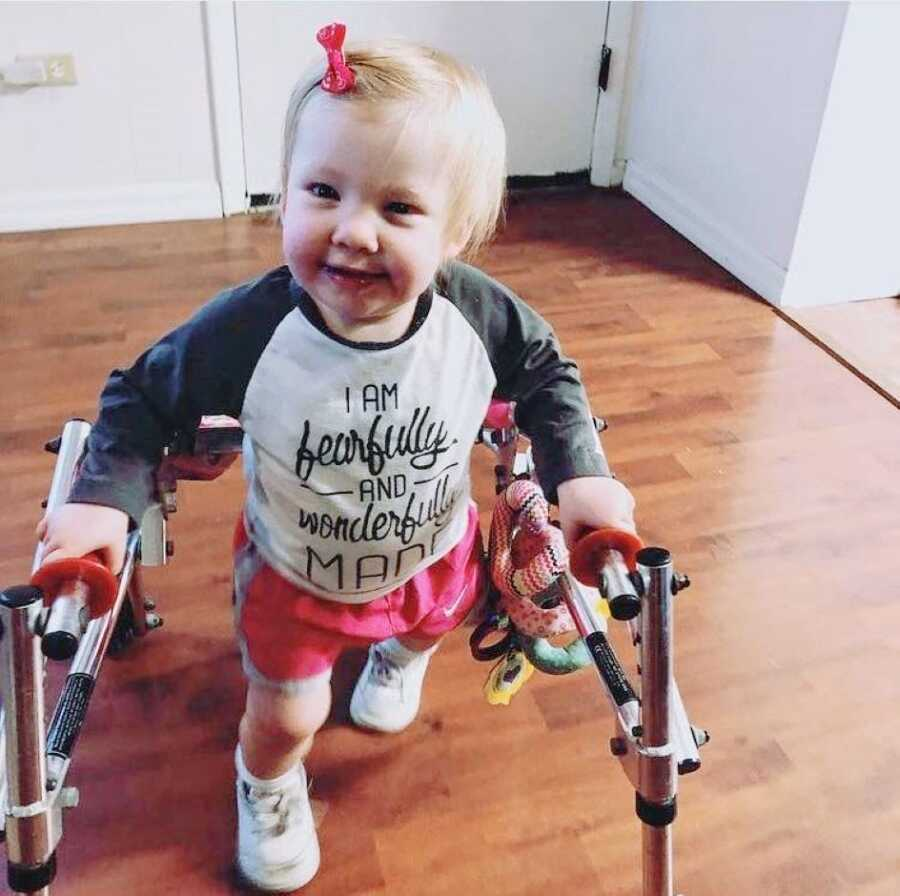 Little girl with rare Coffin-Siris Syndrome practices walking with a walker