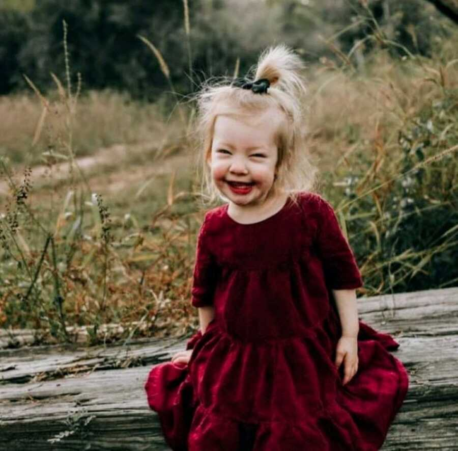 Little girl with Coffin-Siris Syndrome smiles big while wearing a velvet red dress for a Christmas photoshoot