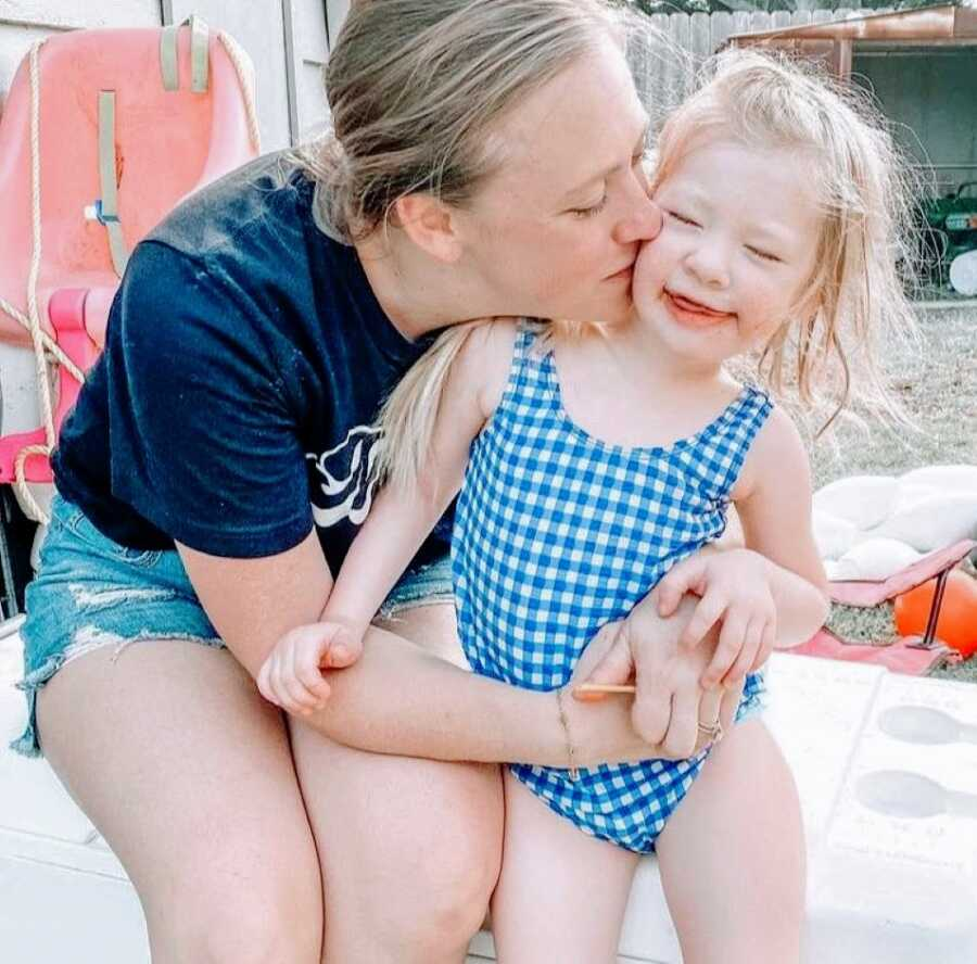 Mom kisses her daughter with Coffin-Siris Syndrome on the cheek while enjoying a pool day in the summer