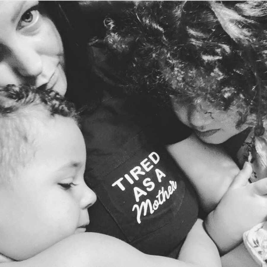 """Single mom cuddles her two children while wearing a shirt that says """"Tired as a mother"""""""