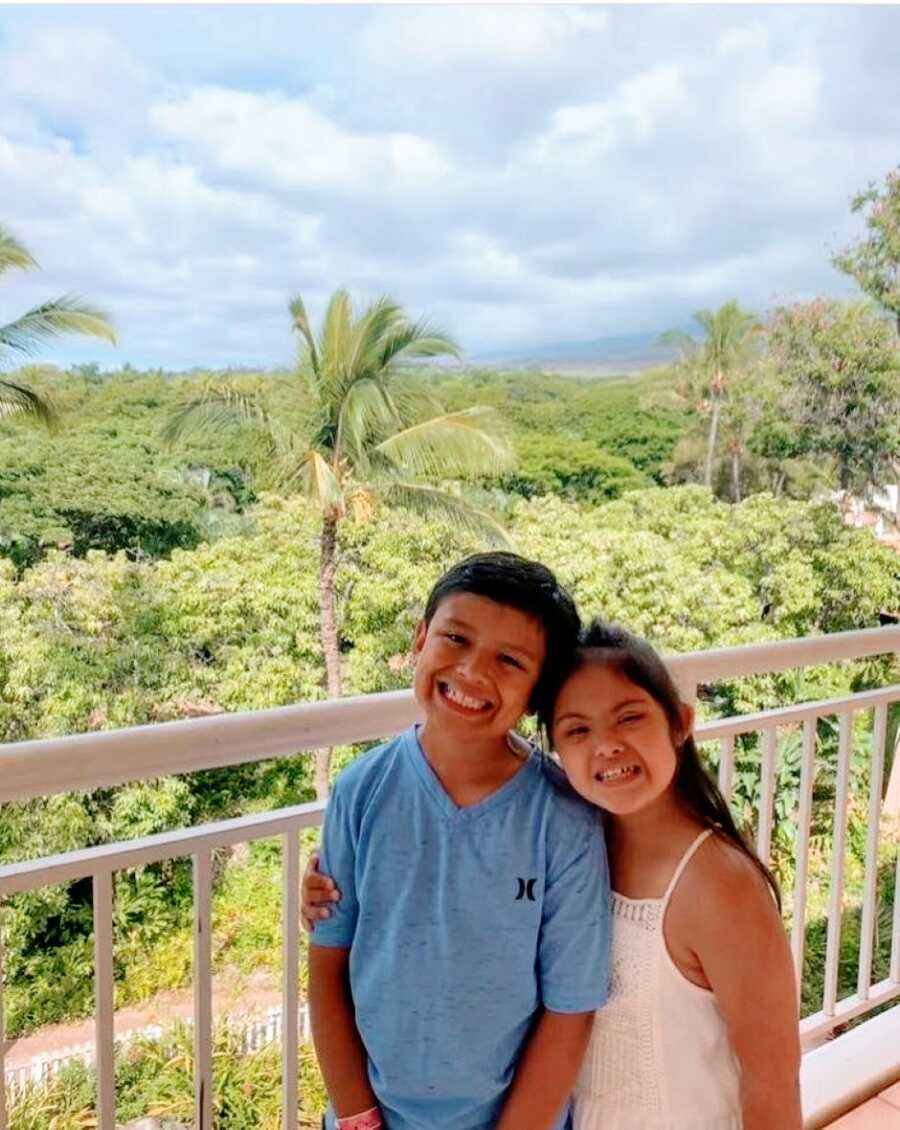 Brother and sister smile big and hug each other while standing on a balcony on a family vacation