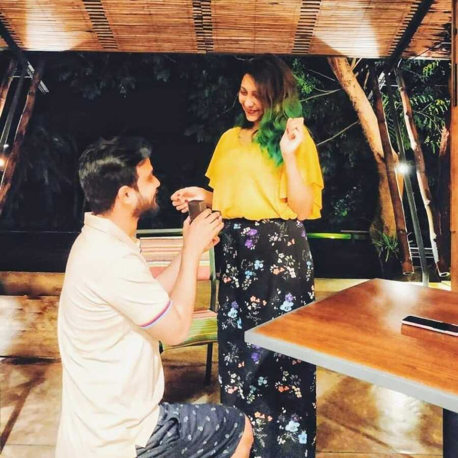 Man gets down on one knee to propose to his wife in romantic setting