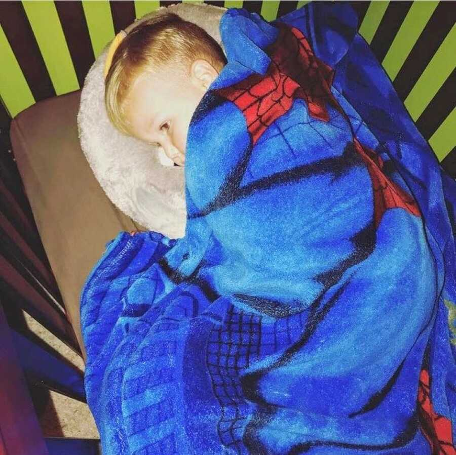 Mom takes a photo of her son sleeping in his bed with a Spiderman blanket after she forgot to take him to school