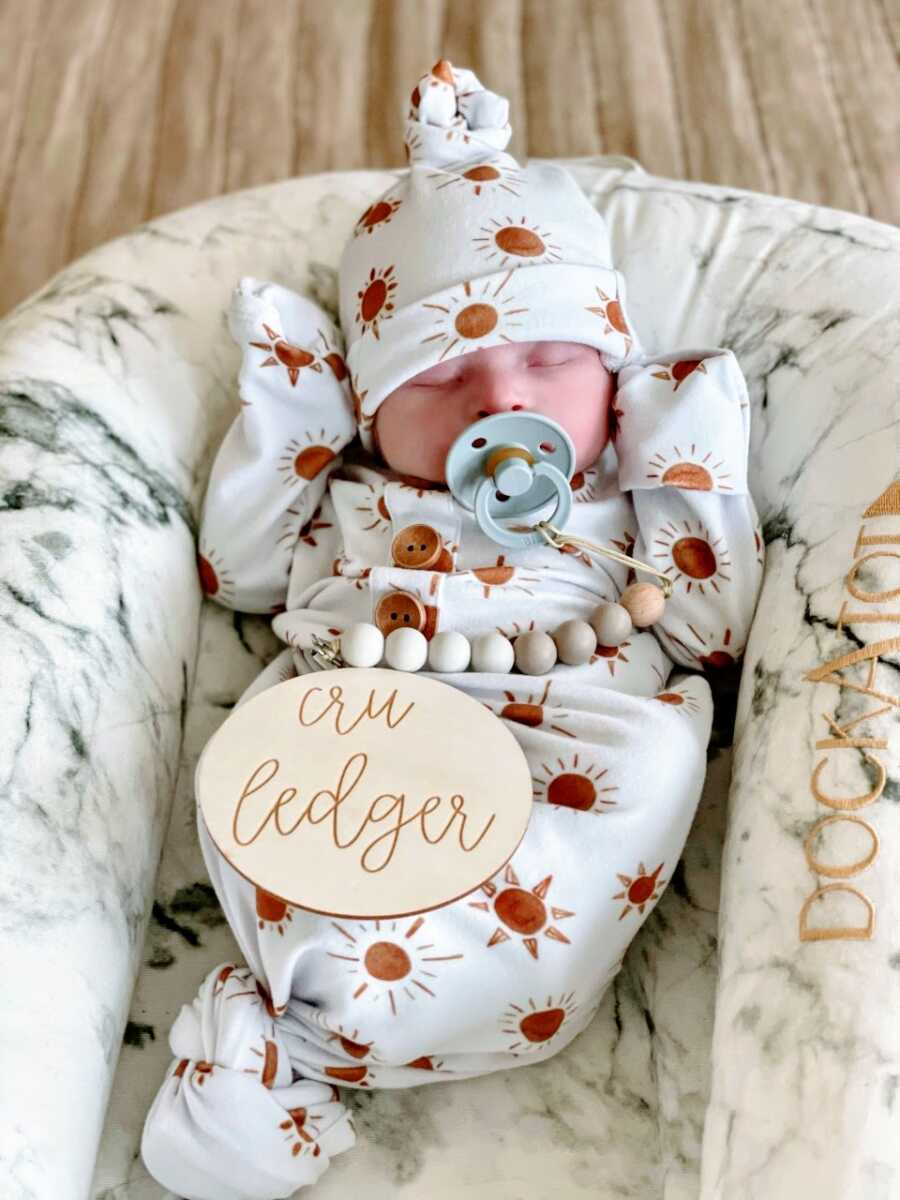 Newborn baby boy sucks a pacifier while wearing a matching onesie and beanie with suns on it