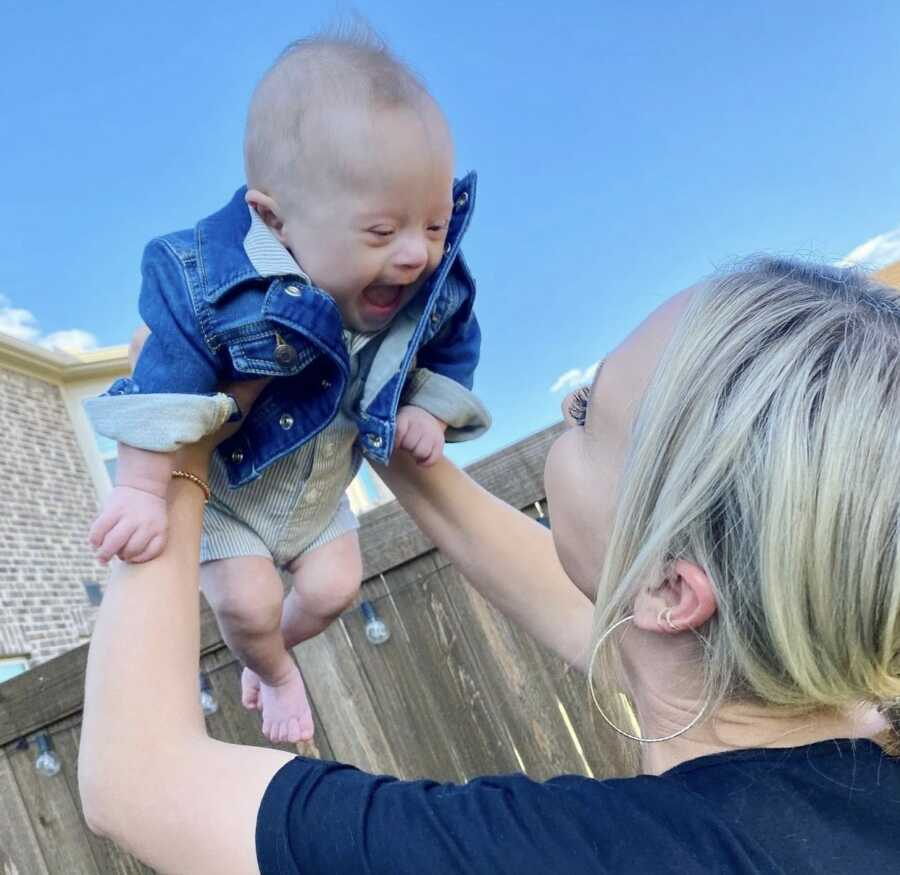 Mom plays airplane in her backyard with her young, happy and smiling son with Down syndrome
