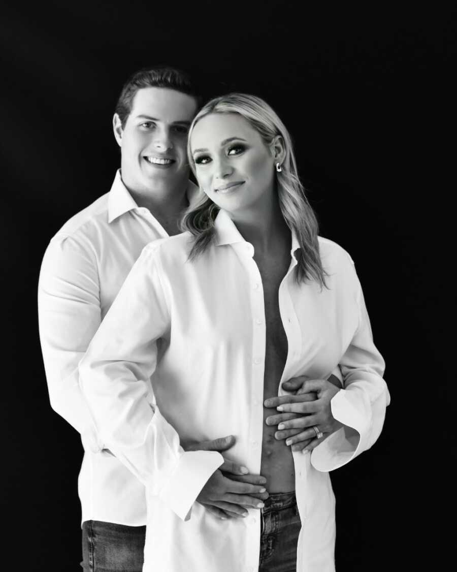 Married couple take black and white maternity photos together in matching white button down shirts