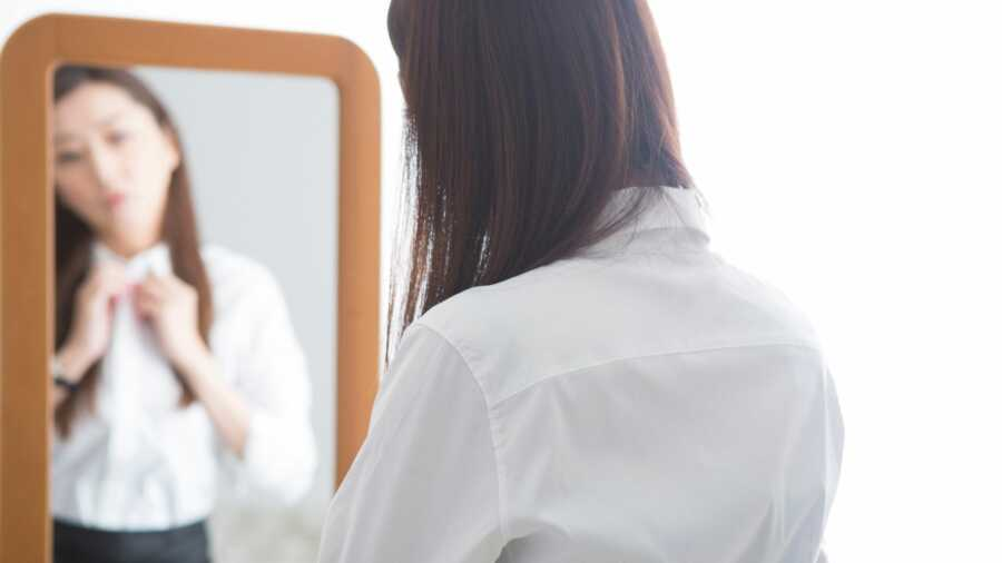 Woman buttons her shirt and examines herself in the mirror.