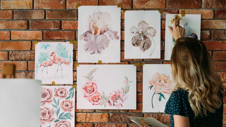 Woman hangs watercolor paintings on a brick wall.