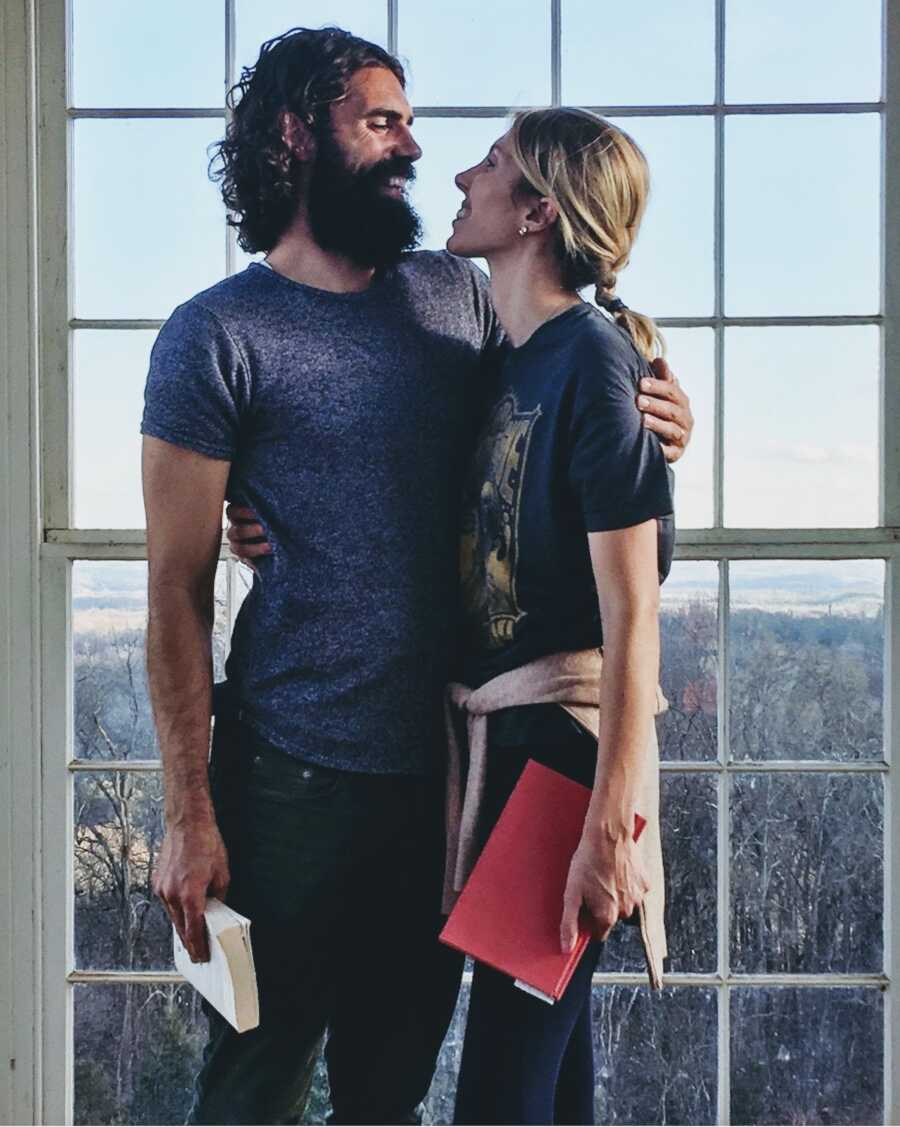 man and woman stand together by window