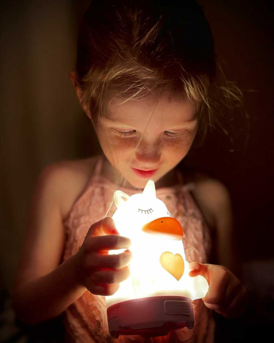A young girl stares in wonder at a glowing night light animal.